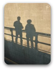 Old photograph - the shadows of a couple standing next to the railing on a board a ship.