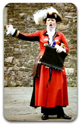 A woman in town-crier costume announcing the news