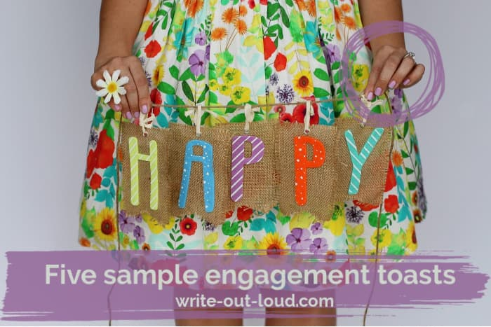 Girl wearing a colorful flowery skirt holding a piece of burlap with the word Happy on it.