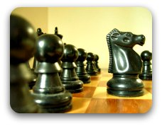 black chess pieces set on polished wooden board