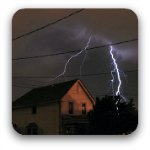 A flash of ligtning over a house on a dark and stormy night.