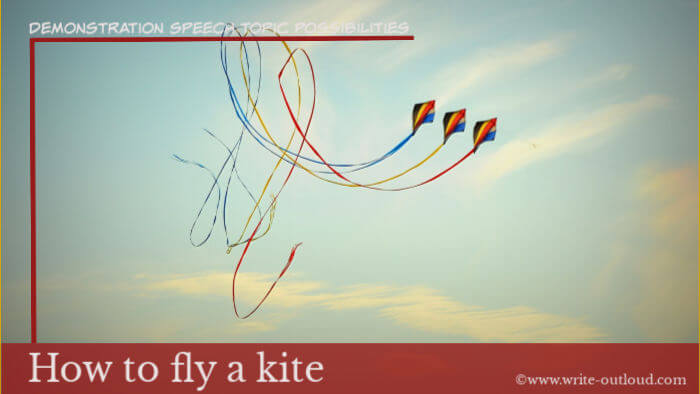 Image: three multi-colored kites against blue sky. Text-Demonstration speech topic-  How to fly a kite.