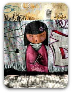 Stylized Japanese doll on a graffiti covered wall