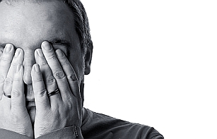 man hiding face with hands