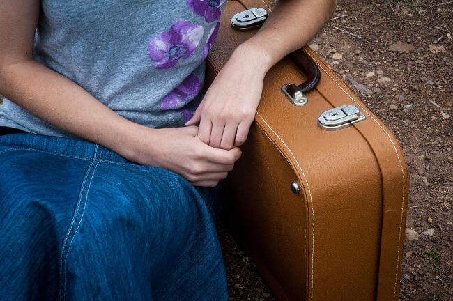 Girl resting her arm on an old-fashioned suitcase