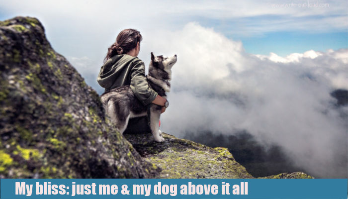 Young woman with her dog sitting on a mountain ledge high above the clouds.